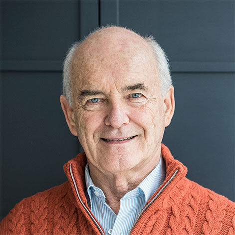 Portrait of an older professional man with an orange cable-knit sweater
