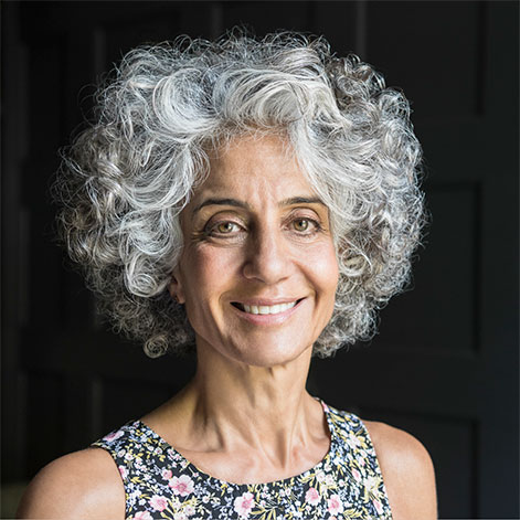 Portrait of an older woman with gray curly hair and a floral top