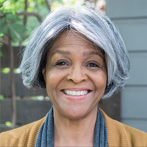 Portrait of an older professional woman with gray hair and a mustard sweater