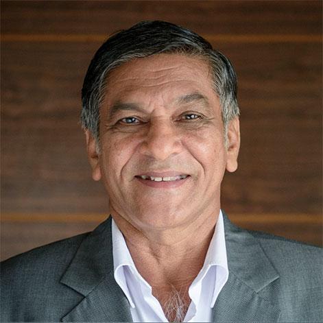 Portrait of an older man in a gray blazer