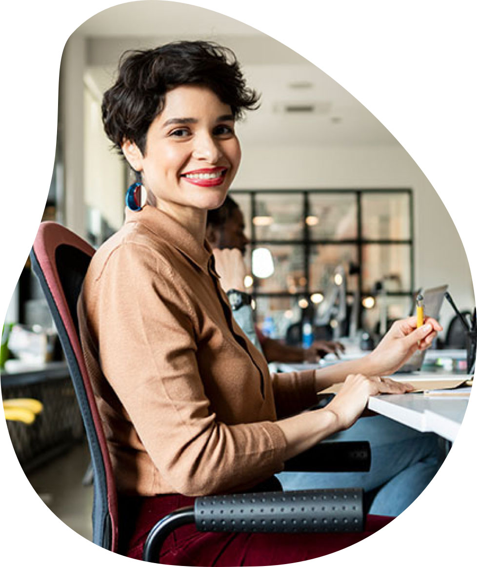 A professional woman smiles and sits at a desk in a modern office