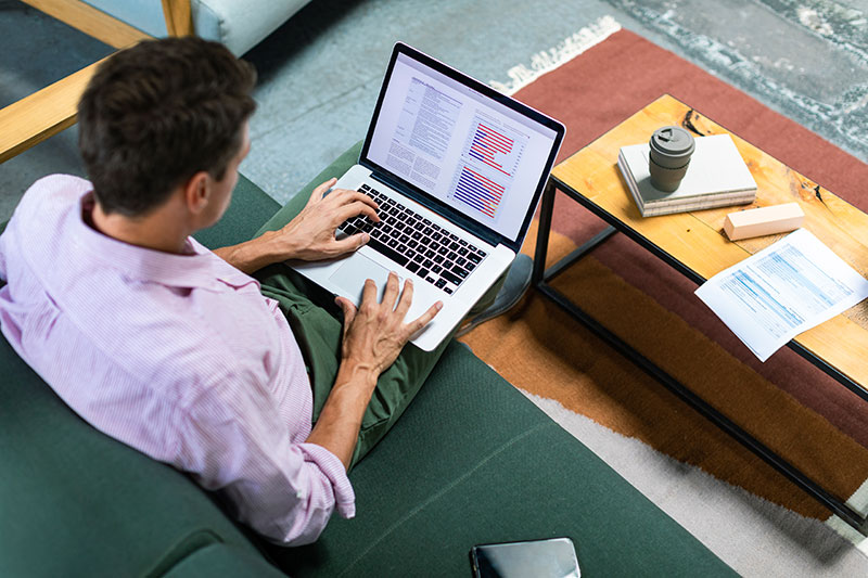 A man works on reports on a laptop