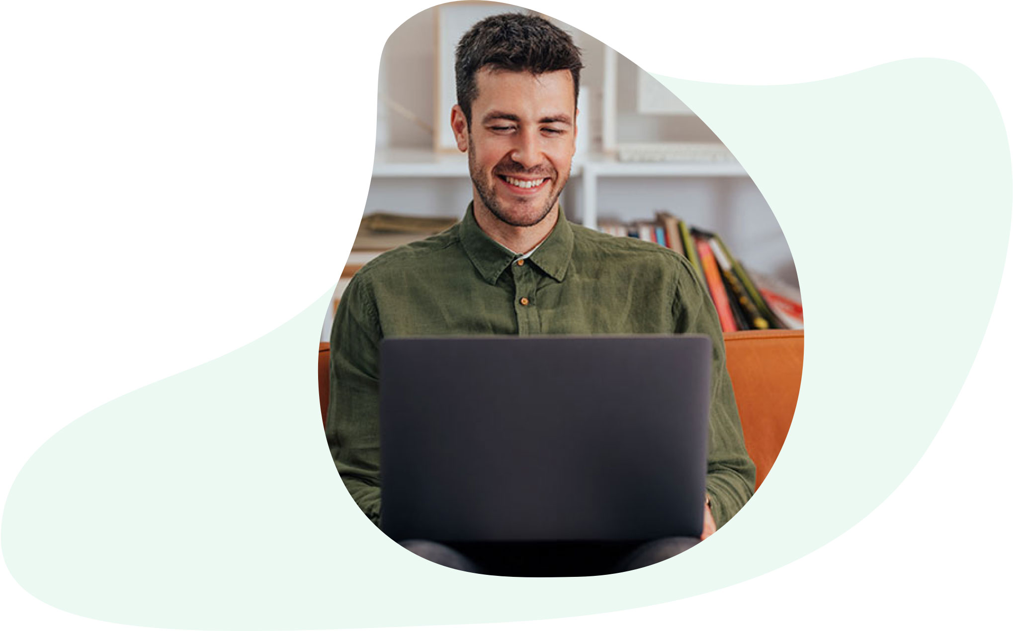 Man wearing a green shirt and working on his laptop