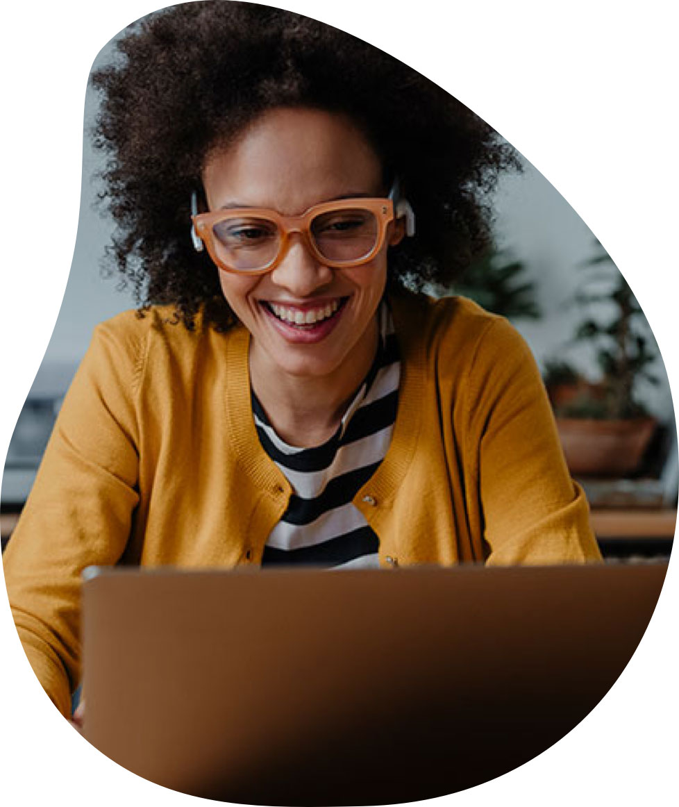 Professional woman with orange glasses smiling and working on her computer